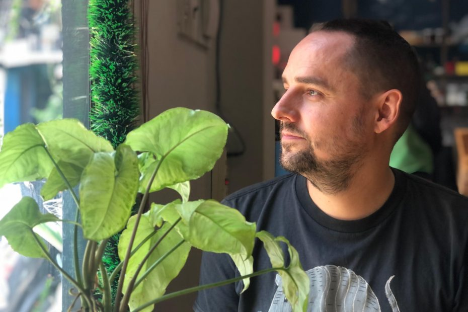 Ryan Patey looking out a window with a plant next to him